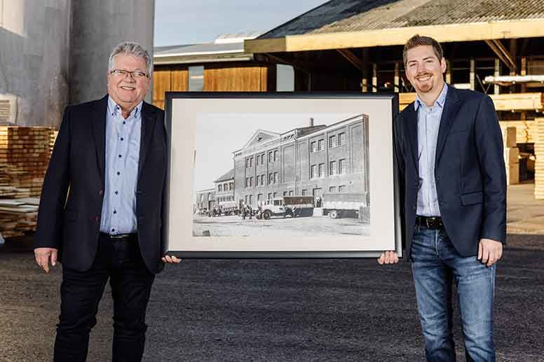 Managing directors holding a historical photograph